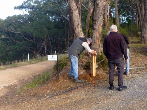 Installing the first post on the Adelaide100 trail, directing walkers along Monument Road between Norton Summit and Debneys Road.