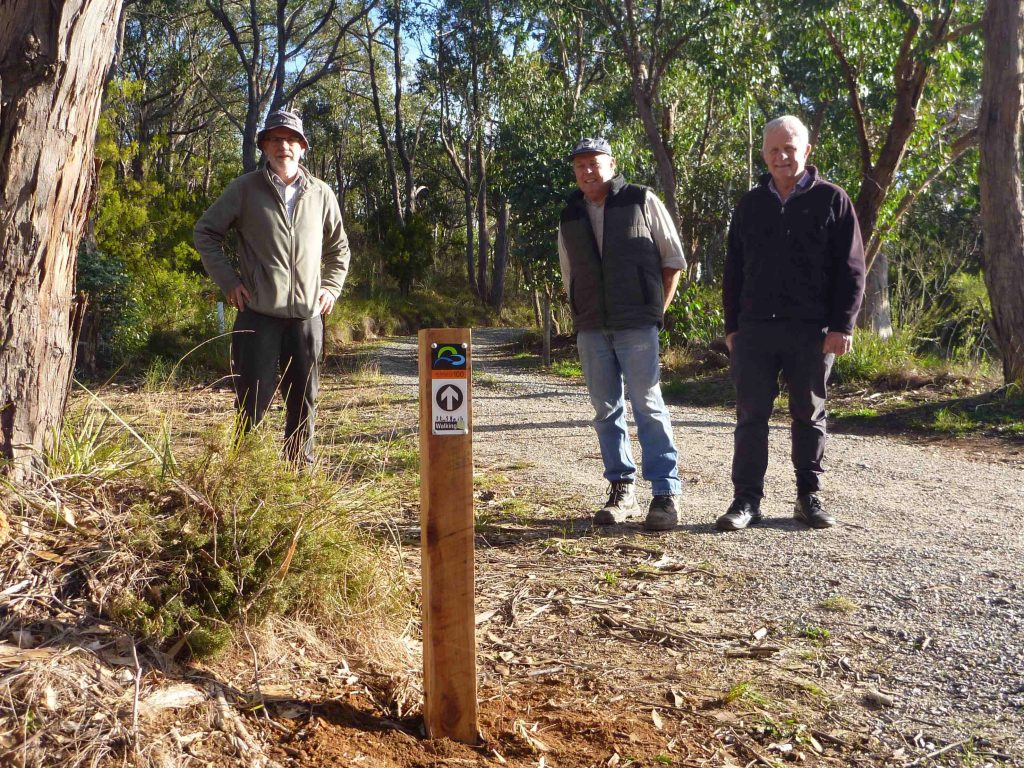 Jim Mclean, trail visionary, with John Potter, from the Friends of the Heysen Trail, and helper Bill Gehling having installed the first Adelaide100 post.